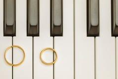 Anillos de bodas en piano Imagen de archivo libre de regalías