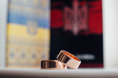 Anillos de bodas en un fondo del símbolo Ucrania Imagen de archivo libre de regalías