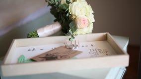 Anillos de bodas en un sobre con una letra con un bouque de la boda almacen de video