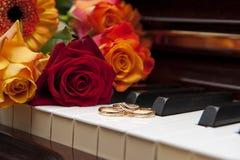 Anillos de bodas en un teclado y las flores de piano Imagen de archivo