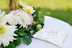 Anillos de bodas en una almohada blanca cerca de las flores Imágenes de archivo libres de regalías