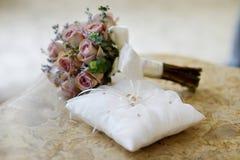 Anillos de bodas en una almohada Fotos de archivo libres de regalías