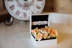Anillos de bodas en una caja en la tabla blanca Concepto de boda Imagen de archivo libre de regalías