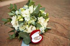 Anillos de bodas en una caja de regalo hermosa y un ramo de la novia Imagen de archivo