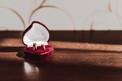 Anillos de bodas en una caja roja en una tabla de madera fotos de archivo libres de regalías