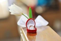 Anillos de bodas en una caja y una flor en forma de corazón Imagen de archivo