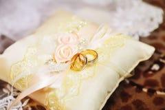 Anillos de bodas en una pequeña almohada Fotografía de archivo