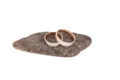 Anillos de bodas en una piedra en un aislamiento blanco del fondo Imagen de archivo