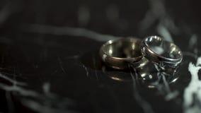 Anillos de bodas en una tabla de piedra de mármol negra Dos anillos en una tabla de mármol negra almacen de metraje de vídeo