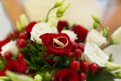 Anillos de bodas de oro entre bayas rojas y rosas blancas y rojas del ramo de la boda Fotografía de archivo libre de regalías