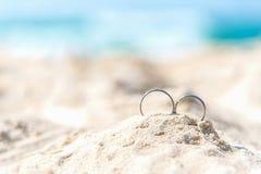 Anillos de bodas para el amante de los pares en la playa arenosa Anillos de compromiso en vacaciones de la luna de miel en las zo imagenes de archivo