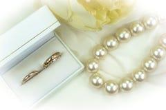 Anillos de bodas, perlas blancas, flor en el fondo blanco Fotos de archivo