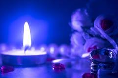 Anillos de bodas por luz de una vela Fotografía de archivo