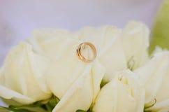 Anillos de bodas que mienten en las rosas blancas Imagenes de archivo