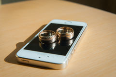 Anillos de bodas que ponen en la pantalla del teléfono celular Imagen de archivo