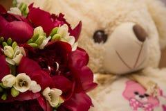 Anillos de bodas que se colocan en un ramo de peonías y de fresias imagen de archivo libre de regalías