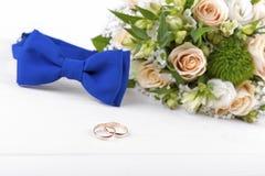Anillos de bodas y accesorios en la tabla de madera blanca Imagen de archivo