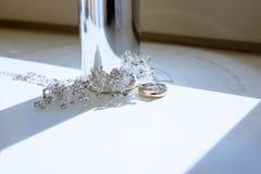 Anillos de bodas y botella de perfume hermosos para la novia y el novio Imágenes de archivo libres de regalías