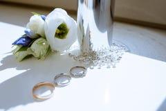 Anillos de bodas y botella de perfume hermosos para la novia y el novio Foto de archivo libre de regalías