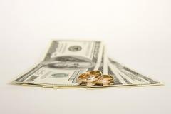 Anillos de bodas y dinero en un fondo blanco Imagen de archivo libre de regalías