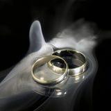 Anillos de bodas y humo de oro Imagenes de archivo