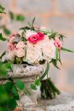 Anillos de bodas y manojo de rosas, de peonías y de succulents en Fotografía de archivo