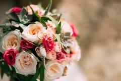Anillos de bodas y manojo de rosas, de peonías y de succulents en Fotos de archivo libres de regalías