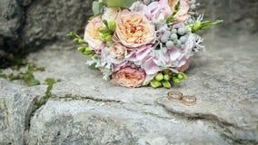 Anillos de bodas y ramo de la boda