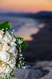 Anillos de bodas y ramo en la puesta del sol Fotos de archivo
