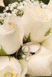 Anillos de bodas y rosas blancas Imagenes de archivo