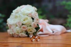 Anillos de bodas y rosas del ramo Fotografía de archivo