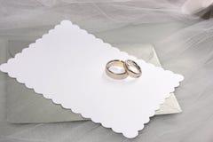 Anillos de bodas y tarjeta en blanco Fotos de archivo libres de regalías
