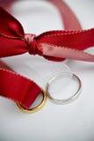 Anillos de bodas y una cinta roja Foto de archivo libre de regalías