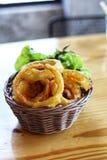anillos de cebolla fritos en cesta de mimbre en la tabla de madera Imagen de archivo libre de regalías