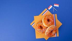 Anillos de espuma anaranjados para el día del ` s del rey del día de fiesta, días de fiesta de Holanda El cocer en un fondo azul  imagen de archivo