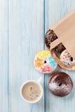 Anillos de espuma coloridos en bolsa de papel y taza de café Foto de archivo libre de regalías