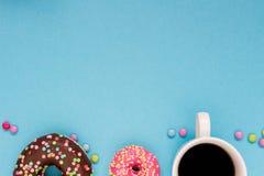 Anillos de espuma dulces con café en el fondo azul Fotografía de archivo libre de regalías
