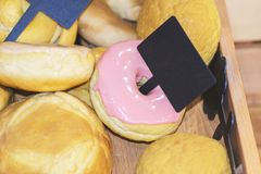Anillos de espuma dulces con helar rosado en la caja con la etiqueta imagenes de archivo