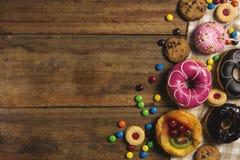 Anillos de espuma, galletas, y queque de frutas redondos, postre plano de la endecha en la tabla de madera Foto de archivo
