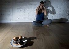 Anillos de espuma malsanos del azúcar y molletes y muchacha tentada de la mujer joven o del adolescente que se sientan en la tier Foto de archivo