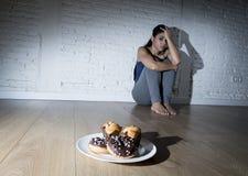 Anillos de espuma malsanos del azúcar y molletes y muchacha tentada de la mujer joven o del adolescente que se sientan en la tier Foto de archivo libre de regalías