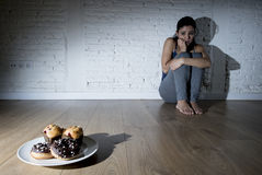 Anillos de espuma malsanos del azúcar y molletes y muchacha tentada de la mujer joven o del adolescente que se sientan en la tier Imagen de archivo libre de regalías