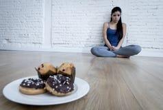 Anillos de espuma malsanos del azúcar y molletes y muchacha tentada de la mujer joven o del adolescente que se sientan en la tier Imagen de archivo