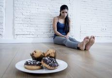 Anillos de espuma malsanos del azúcar y molletes y muchacha tentada de la mujer joven o del adolescente que se sientan en la tier Fotos de archivo