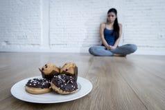 Anillos de espuma malsanos del azúcar y molletes y muchacha tentada de la mujer joven o del adolescente que se sientan en la tier Fotografía de archivo