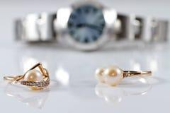 Anillos de oro con las perlas de diversos estilos en el wat del fondo Foto de archivo libre de regalías