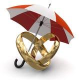 Anillos de oro debajo del paraguas (trayectoria de recortes incluida) Foto de archivo libre de regalías