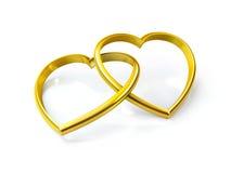 Anillos de oro en forma de corazón Fotografía de archivo libre de regalías