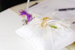 Anillos de oro en la almohada de la boda Foto de archivo