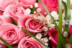 Anillos de oro y ramo color de rosa imagenes de archivo